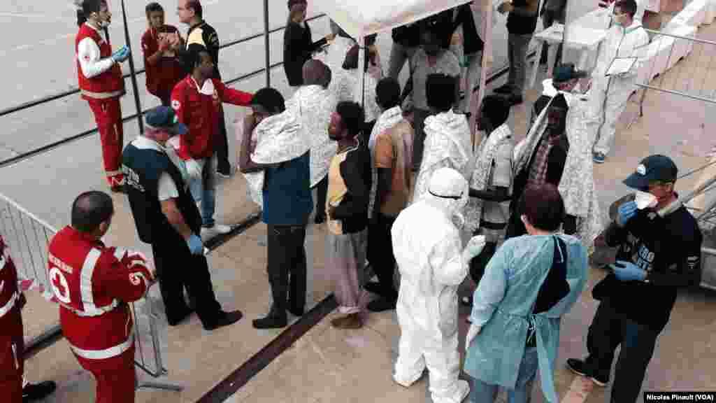 Des volontaires de la Croix rouge et des personnels de santé examinent les migrants à la descente du bateau, Messine, Sicile, 6 octobre 2015 (Nicolas Pinault/VOA).