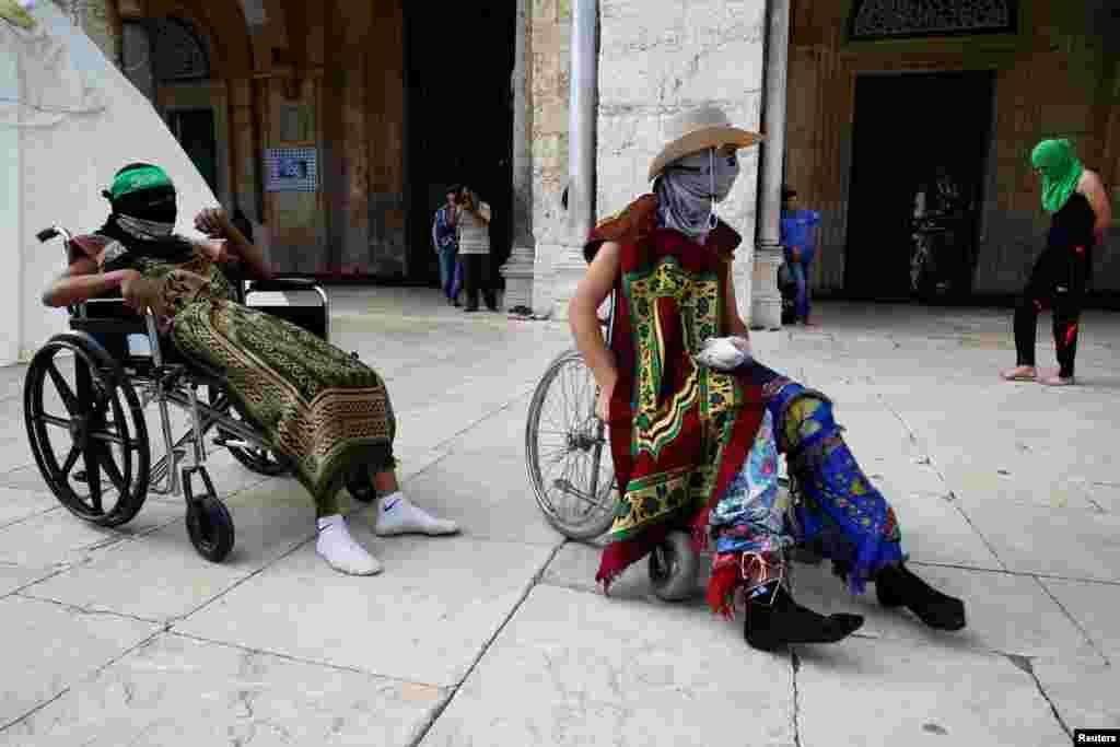 Dua pria Palestina yang mengenakan topeng beristirahat di kursi roda, sebelum pecah bentrokan dengan polisi Israel di Haram Area di komplek Al-Aqsa di kota kuno Yerusalem.