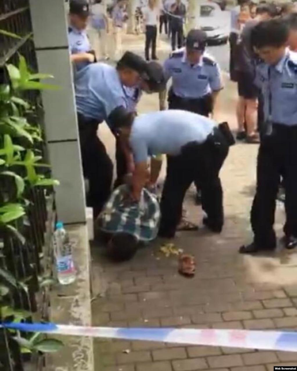 2018年6月28日,上海市警方人員在上海世界外國語小學校門外的案發現場控制涉案者(網絡照片)