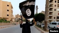 FILE - A member loyal to the Islamic State waves an IS flag in Raqqa, June 29, 2014.