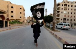 A member of the Islamic State carries the militant group's signature black flag in Raqqa, Syria in 2014.