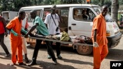 A wounded man is being carried into the General Hospital in Bangui on Sept. 26, 2015, after unknown assailants opened fire in the PK5 district, a neighborhood with a majority of Muslim residents.