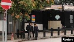 Tiga orang menunggu di depan bagian permohonan visa Kedutaan Besar AS di Ankara, Turki, Senin (9/10).