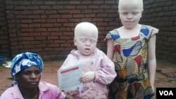 Une femme pose avec ses deux enfants albinos au Malawi. (L. Masina/VOA)