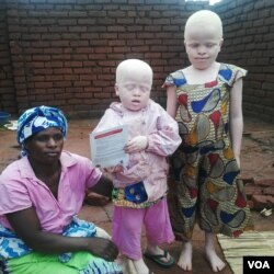 A woman poses with her children with albinism in northern Malawi. (L. Masina/VOA)