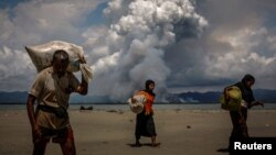 FILE - Smoke is seen on the Myanmar border as Rohingya refugees walk on the shore after crossing the Bangladesh-Myanmar border by boat through the Bay of Bengal, in Shah Porir Dwip, Bangladesh, Sept. 11, 2017.