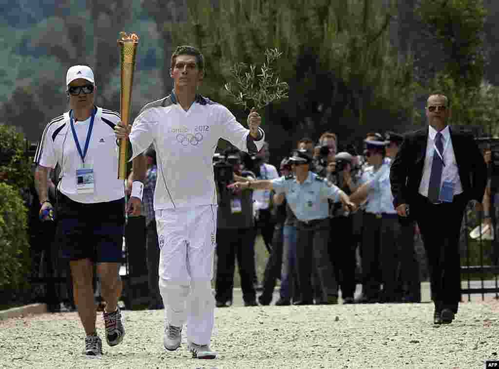 Spyridon Gianniotis, Greece's world champion of swimming, runs with the Olympic flame and an olive branch during the Olympic torch relay. (Reuters)