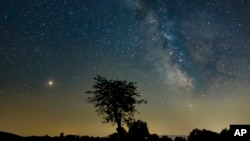 FILE - Mars, left, and the Milky Way are visible in the clear night sky as photographed near Salgotarjan, some 110 kms northeast of Budapest, Hungary, Aug. 03, 2018.