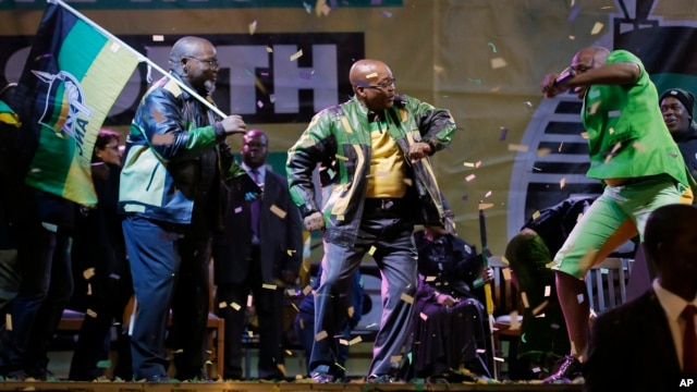 The ruling party president Jacob Zuma, center, sings and dances,  at a victory party downtown Johannesburg, South Africa,  following the announcement of the results for the 2014 national election result Saturday May 10, 2014