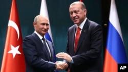 Presiden Turki Recep Tayyip Erdogan, kanan, and Presiden Rusia Vladimir Putin berjabat tangan setelah konferensi pers bersama di Ankara, Turki, 28 September 2017.
