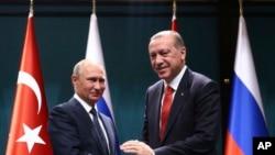 Midigta waxaa taagan madaxweynaha Turkiga Recep Tayyip Erdogan, wuxuu gacan qaadaya dhiggiisa Russia Vladimir Putin, waxay Khamiisti shir jaraa,id ku wada qabteen Ankara, Turkey, Sept. 28, 2017.
