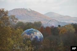 Un globo y una rueda moscovita se aprecian en un bosque cerca de Bonn, en Alemania, donde se lleva a cabo la Conferencia Marco de la Convención de la ONU sobre el Cambio Climático, hasta el 17 de noviembre.