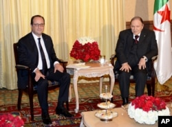 FILE - French President Francois Hollande, left, and Algerian President Abdelaziz Bouteflika, right, pose prior to a meeting in Algiers, June 15, 2015.
