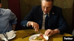 Republican presidential hopeful John Kasich is seen eating pizza with a fork in this photo posted on Twitter. (Twitter)