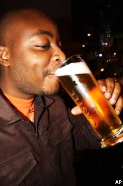 Webster Dladla swigs a beer at his favorite drinking hole in Johannesburg....He has tickets for the South Africa-Uruguay game.....