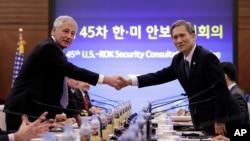 El secretario de Defensa de Estados Unidos, Chuck Hagel (izquierda) sella con un apretón de manos con su contraparte coreana, Kim Kwan-jin, un acuerdo de defensa contra Corea del Norte.