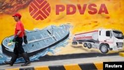 Un trabajador camina frente a un mural con el logo de PDVSA, en una estación en Caracas.