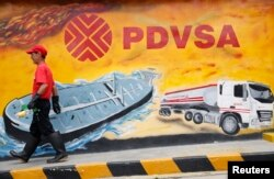 FILE - A worker walks past a mural with a PDVSA logo at its gas station in Caracas, Aug. 29, 2014.