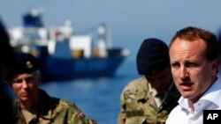 "Denmark's Foreign Minister Martin Lidegaard (r) speaks to the Danish sailors aboard the Danish warship ""Esbern Snare"" which is escorting the cargo ships that are transporting Syria's most dangerous chemical weapons, May 13, 2014."