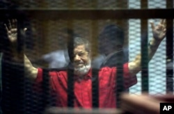 Former Egyptian President Mohamed Morsi, wearing a red jumpsuit that designates he has been sentenced to death, raises his hands inside a defendants cage in a makeshift courtroom at the national police academy, in an eastern suburb of Cairo, June 18, 2016.