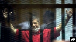 Former Egyptian President Mohamed Morsi, wearing a red jumpsuit that designates he was sentenced to death, raises his hands inside a defendants cage in a makeshift courtroom at the national police academy, in an eastern suburb of Cairo, Egypt, Saturd