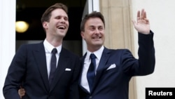 Luxembourg's Prime Minister Xavier Bettel waves as he poses with his partner, Belgian Gauthier Destenay, after their wedding ceremony at Luxembourg's city hall, May 15, 2015.