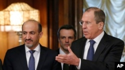 Russian foreign minister Sergey Lavrov, right, welcomes Ahmad Jarba, left, who heads a delegation of the Syrian National Coalition prior talks in Moscow, Feb. 4, 2014.