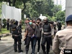 Seorang pemuda yang diamankan polisi terkait unjuk rasa berujung anarkis di gedung DPRD Sumut, Kota Medan, Kamis 8 Oktober 2020. (VOA/Anugrah Andriansyah)