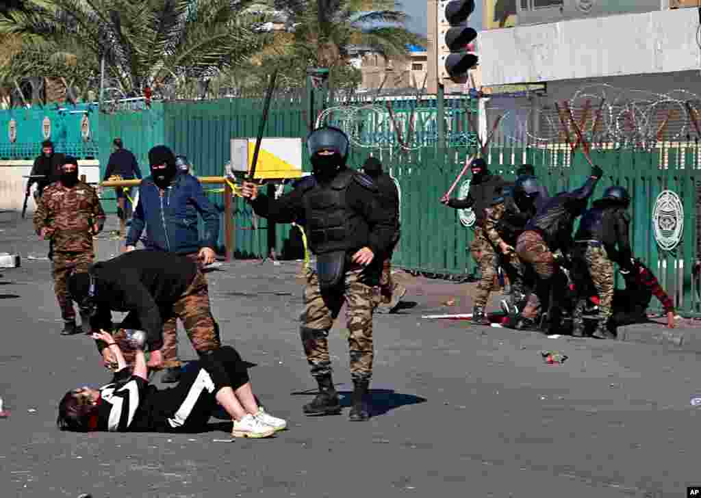 A riot policeman pins down a female anti-government protester to search her while security forces disperse demonstrators during clashes in Baghdad, Iraq.