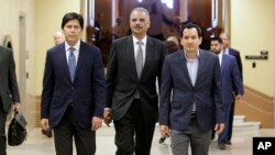 FILE - Former U.S. Attorney General Eric Holder, center, flanked by California Senate President Pro Tem Kevin de Leon, D-Los Angeles, left, and Assembly Speaker Anthony Rendon, D-Paramount, walks to a meeting with California Gov. Jerry Brown in Sacramento, California, Feb. 7, 2017.