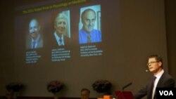 El momento del anuncio de los ganadores del Nobel de Física, el estadounidense Saul Perlmutter, su compatriota Adam Riess y el australiano-estadounidense Brian Schmidt.