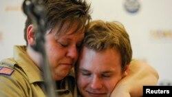 Jennifer Tyrrell (kiri), yang dipecat dari Pramuka AS karena ia gay, memeluk Pascal Tessier, 16, setelah munculnya keputusan pencabutan larangan anak laki-laki gay menjadi anggota Boy Scouts of America (24/5). (Reuters/Michael Prengler)