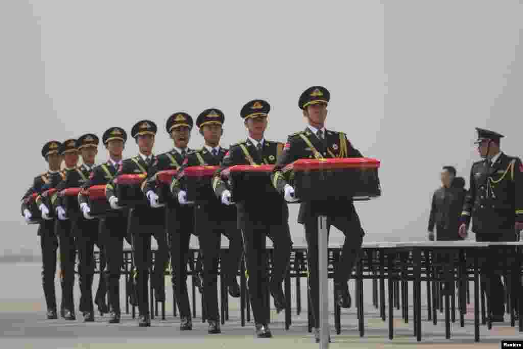 ទាហានកិត្តិយសចិនលើកមឈូសប្រគល់ត្រលប់មកវិញដោយប្រទេសកូរ៉េខាងត្បូង ដែលមឈូសនេះមានផ្ទុកបំណែកសាកសពទាហានចិន ដែលត្រូវបានសម្លាប់នៅអំឡុងពេលសង្រ្គាមកូរ៉េរវាងឆ្នាំ១៩៥០ និង១៩៥៣ នៅឯព្រលានយន្តហោះមួយនៅក្រុង Shenyang ខេត្ត Liaoning។