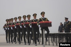 中国仪仗队在辽宁省沈阳市的一个机场抱着由韩国归还的装有中国军人遗骸的盒子。那些死者在1950年至1953年的朝鲜战争中丧生。(2016年3月31日)