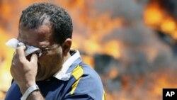 在开罗内政部前一位遭到催泪弹袭击的抗议者在擦眼泪