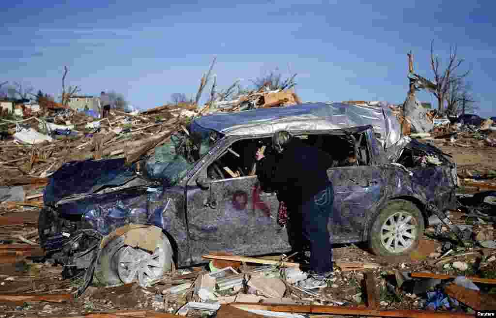 미국 일리노이주 워싱턴 카운티의 한 주민이 토네이도가 강타한 자택으로 19일 돌아왔다. 폐허가 된 집터에서 손상된 차를 들여다보고 있다.