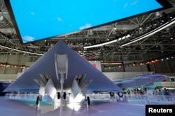 广东珠海中国国际航空航天博览会上展出的攻击-11隐形无人战斗机,右后是首次展出的中国空军最先进的歼-20战机。(2021年9月29日)
