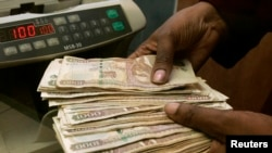FILE - Cashier counts Kenya shillings in Nairobi. A new report says more than 40 percent of Kenyans cannot afford to retire and must continue working.