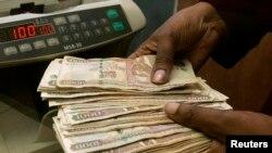 Seorang petugas tengah menghitung mata uang Kenya di sebuah tempat penukaran valuta asing di Nairobi, Kenya (Foto: dok). Pemerintah Kenya telah membekukan rekening bank 86 badan hukum dan perorangan yang dicurigai membiayai terorisme.