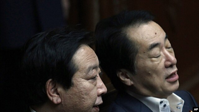 Japanese Finance Minister Yoshihiko Noda (L) talks with Prime Minister Naoto Kan before a regular session at the lower house of parliament in Tokyo, June 9, 2011