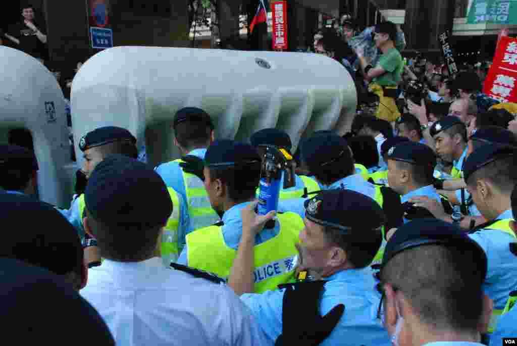 大批示威者不满示威区范围太小企图推倒水马阵防线,与香港警方发生冲突,有香港警员手持胡椒喷雾(蓝色罐)
