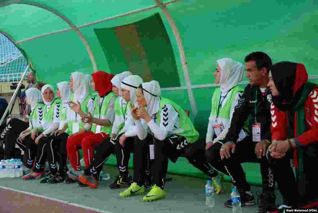 افغان خواتین کے اسکواڈ میں شامل کھلاڑی اپنی ٹیم کو کھیلتا دیکھ رہی ہیں۔