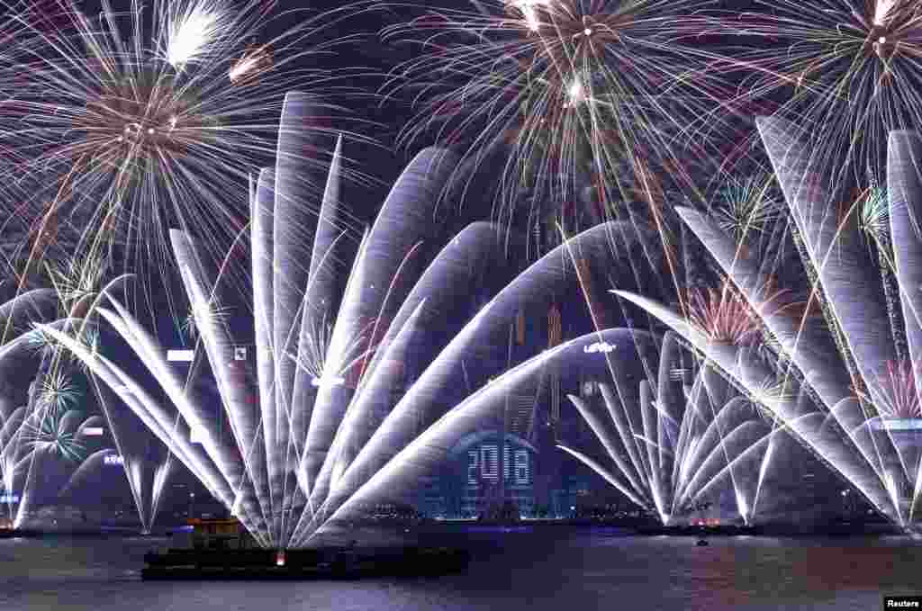 Fireworks explode over Victoria Harbour and Hong Kong Convention and Exhibition Centre to celebrate the New Year, Jan. 1, 2018.