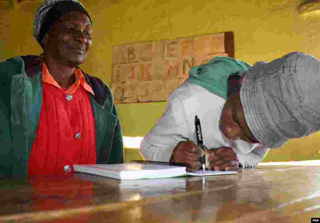Sinesipho Makala writes her name, watched by her grandmother, Nozinzile (VOA/ D. Taylor)