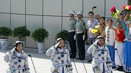 China's astronauts salute before they depart for the Shenzhou 9 spacecraft rocket launch pad at the Jiuquan Satellite Launch Center in Jiuquan, China, June 16, 2012 (AP).