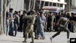 Un soldado de la OTAN defiende a los civiles que se protegen de los disparos en Kabul, durante el ataque de este domingo.