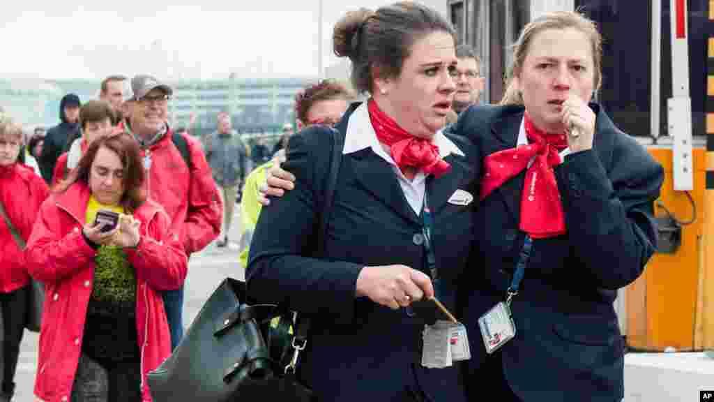 比利时布鲁塞尔国际机场发生多起爆炸后,人们撤离现场。( 2016年3月22日)
