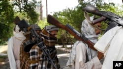 FILE - In this July 31, 2011 file photo, Taliban fighters hold their heavy and light weapons before surrendering them to Afghan authorities in Jalalabad, east of Kabul, Afghanistan.