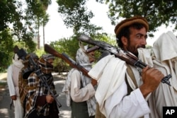 FILE - Taliban fighters hold their heavy and light weapons before surrendering them to Afghan authorities in Jalalabad, east of Kabul, Afghanistan.