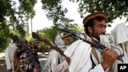Taliban fighters, seen in this 2011 file photo, hold their heavy and light weapons before surrendering them to Afghan authorities in Jalalabad, east of Kabul, Afghanistan.